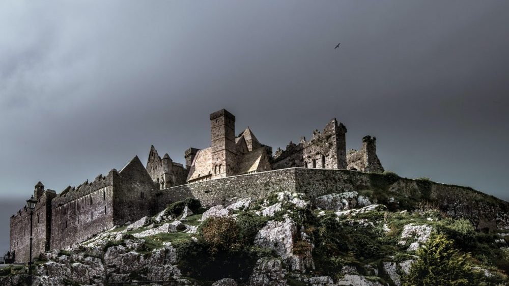 brown concrete castle under black clouds during daytime